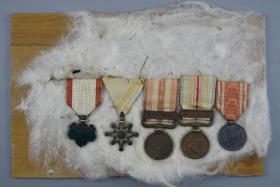 侵华史料《日本勋章》日本军人勋章五枚 包括:勋八等瑞宝章一枚、支那事变从军记章一枚、昭和六年乃至九年事变从军记章一枚、勋七等青色桐叶章一枚、明治二十一年日本赤十字社一枚 所有勋章均由白线固定在胶合板上