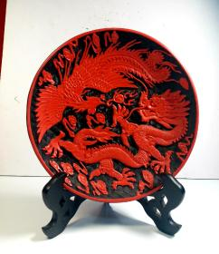 The lacquer red hand-carved dragons and phoenixes show the picture: the diameter of the plate is 19cm and the weight is 347 grams. The carved dragon and phoenix pattern is exquisite and beautiful. The clouds are covered with dragons and phoenixes.