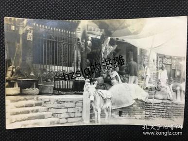 民国民俗风情北京某路边市场及居民、毛驴等景象,可见售卖的各种时令土产和杂货店商品、有一老人正在剃发