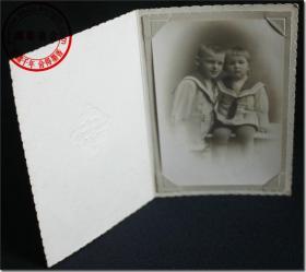 【1940年代后期一对着海军礼服式样服装德国小男孩合影原版黑白老照片】,照片尺寸:11.7厘米×7.8厘米,照片右下角钤英文签名钢印,带照相馆原装相片卡,相片卡加盖有照相馆钢印图标,相片卡尺寸(长×宽):13.5厘米×9.3厘米。照片拍摄于第二次世界大战后期德国的美军占领区(GERMANY US-ZONE),用德国名牌Franka Solida Ⅰ型皮腔风琴折叠式古董照相机拍摄。