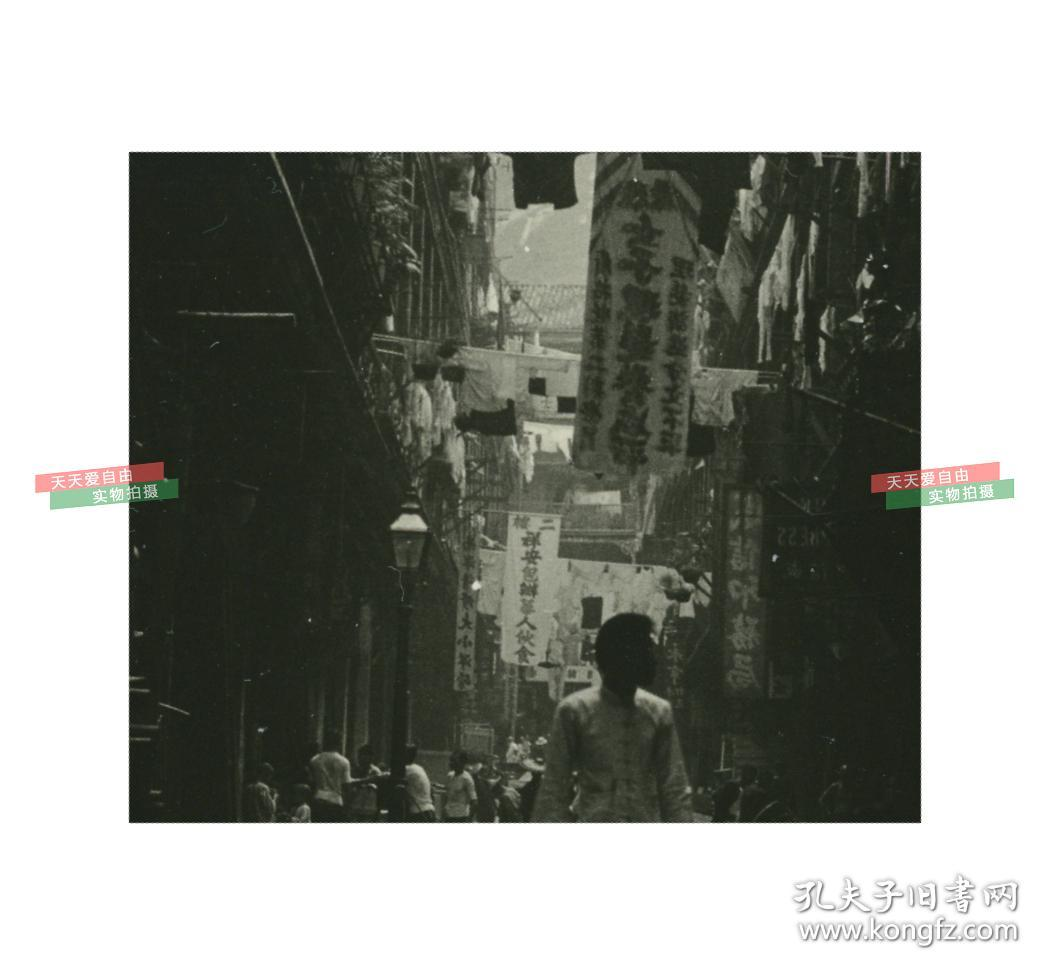 民国时期中国南方的一条街道老照片,后面有起伏的山峦
