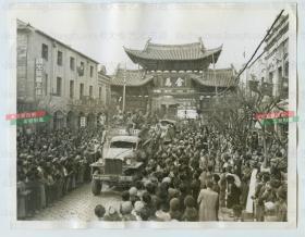 民國1945年中印公路首次開通后,云南昆明群眾在金馬牌坊下熱烈歡迎首批抵達的卡車,可見路旁的國光藝術人像照相館