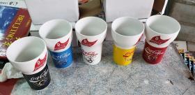 可口可乐北京奥运纪念杯5色一套,独立包装纸盒(已开始松散),送一个手提袋(有皱褶痕及有点污迹),应该是装这些杯的!还有一张可口可乐的名片!