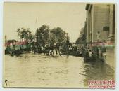 民国湖北汉口大洪水淹没了外滩的道路老照片,人们架木桥从旁边银行建筑中抢救物资