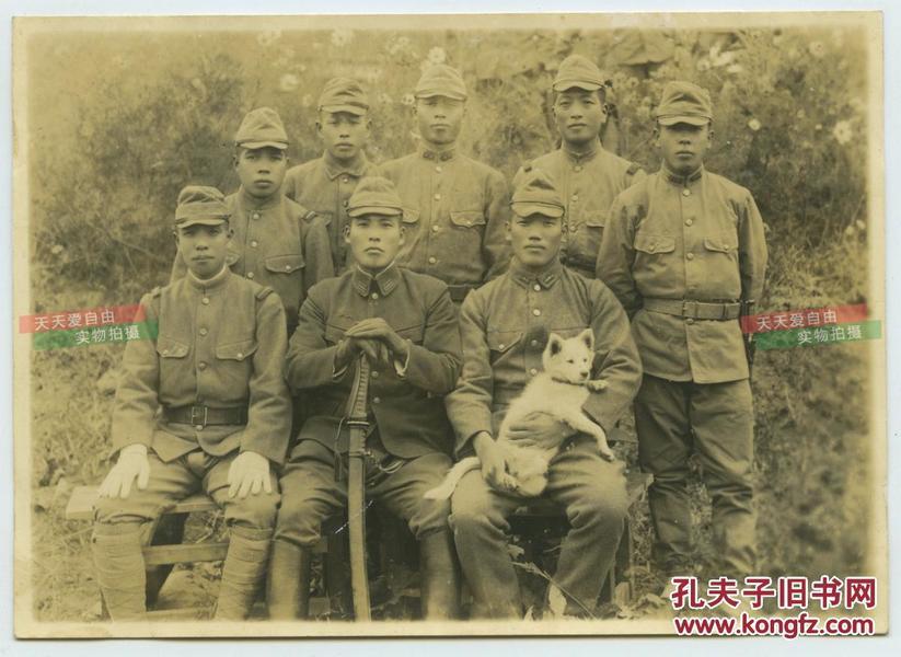 民国侵华日军小队合影,中间的头目手持军刀,右侧一士兵抱着一只小狗,13.9X9.9厘米