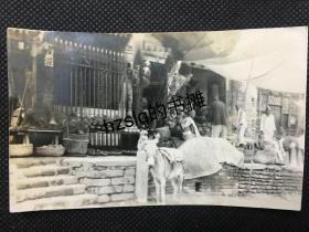 【民俗风情照片】民国北京某路边市场及居民、毛驴等景象,可见售卖的各种时令土产和杂货店商品、有一老人正在剃发。内容少见、颇为难得