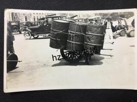 民国早期上海或某大城市里独轮车上的铁皮大油桶及周边景象,颇为有趣