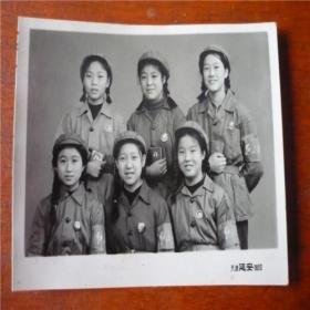 六位头戴绿军帽臂戴红袖章胸戴毛主席像章手捧红宝书的小姑娘的合影