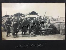 民国初期天津街头一群正卖力拉货的劳工及周边景象,可见一留长辫的男子坐在一旁用餐、边上放有大木桶等,内容生动写实、极有感染力