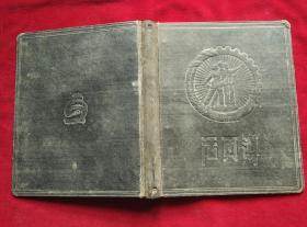 """五十年代老旧活页夹。封面凸起图案为工农兵齿轮麦穗圆徽形,下边凹下三字""""活页簿""""。"""