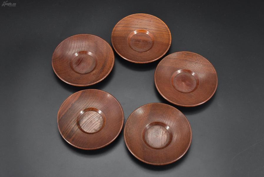 (乙2989)《日本传统工艺漆器》一套五件全 茶托 木胎漆器 木纹理清晰 茶托直径为:12cm 高:2.2cm 公元前二百多年中国的漆艺就开始流传到日本,由于地理环境相似,日本也组织起了漆器生产,形成了日本独特的漆器风格。