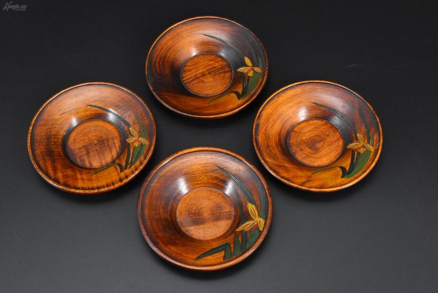 (乙2986)《日本传统工艺漆器》一套四件 茶托 木胎漆器 木纹理清晰 边缘雕兰花 茶托直径为:12cm 高:2.2cm 公元前二百多年中国的漆艺就开始流传到日本,由于地理环境相似,日本也组织起了漆器生产,形成了日本独特的漆器风格。