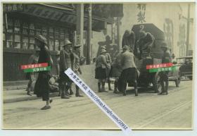1932年淞沪抗战期间,驻守在上海公共租界的各国士兵联合起来协同防御,在南京路酱园一带街道上往装甲车上抬沙袋老照片,旁边可见专售果品罐头的商号。