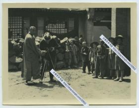 民国时期访问河北张家口的外国摄影师,架设起相机拍照,很多中国当地儿童好奇围观老照片。10.8X8.2厘米,泛银