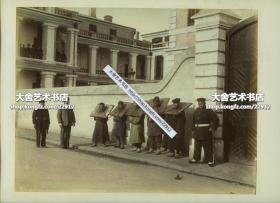 """清代上海租界工部局警署大楼前的巡捕警察和戴枷犯人手工上色大幅蛋白照片,注意犯人枷锁之上书:""""上海县正堂""""字样。25.7X19.7厘米"""