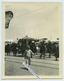 """民国时期街头街景,一支行进中的八抬大轿队伍,并挂有""""加官进爵""""条幅,一个小男孩向摄影师阔步走来老照片。背面有英文""""奉天(沈阳)的文字"""",看有轨电车车辙也很有可能拍摄于北京前门大街。"""