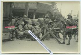 """1932年淞沪抗战期间,驻守在上海公共租界的英国士兵架驻守在路障之后,守卫在租界入口老照片,附近可见""""源记号""""商铺以及当铺标志牌等。15.1X10.1厘米,泛银"""