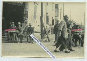 1932年淞沪抗战期间,驻守在上海公共租界的英国士兵架设起路障,守卫在租界入口老照片,一中国女人正带孩子走过。14.8X10厘米,泛银