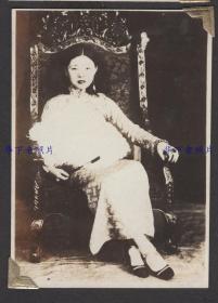 1930年代,伪满洲国,1个穿旗袍的少妇坐在椅子上。