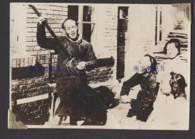 1930年代,伪满洲国,街头艺人坐在椅子上弹奏乐器。