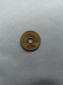 日本硬币 五元 稻穗、水和齿轮图案 日本国 平成八年(1996年) 圆形圆孔钱 原光转光 赠钱币保护盒 稻穗、水和齿轮,分别代表着农业、水产业和工业。而背面则是双叶造型。不过,5日元是日本各面值中不多见的有孔硬币