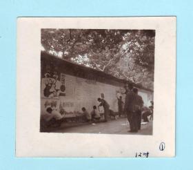 1974年庆祝国庆青年学生正在墙上张贴宣传画报黑白照片,宣传画报内容有十一诗刊、教育革命开新花、红太阳颂、放声唱歌等,照片长7.6厘米,宽6.6厘米