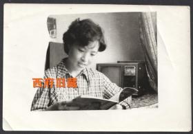 以老式电视机为背景,看画报的格子衫女孩儿