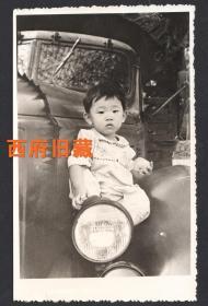 七八十年代,坐在汽车大灯上小孩子,背有揭薄