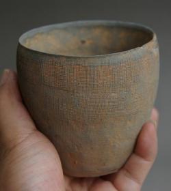 战国细麻布纹蛋壳硬陶杯,浙江窑口出,非常开门的高古陶,距今2000多年了,这么薄无裂线真是奇迹,没变形也是奇迹,纹饰线条间隙仅半毫米左右,也是奇迹。瓷化程度很高,含铁量高,叩击声如磬。当时的贵族用品,市面上极少见,此杯在同类品中已算高大,不常有的,珍之!错过了不知要等多少年,沁色自然,包浆醇厚,精美异常,绝世珍品,吉祥富贵,值得永久收藏的可遇不可求的珍品,孤品,神品