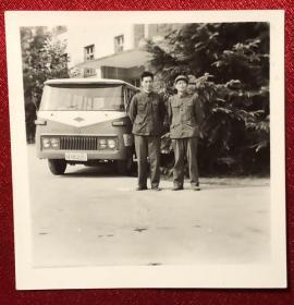 二位军人于军用客车前合影,军车为亥字头铁道兵车牌