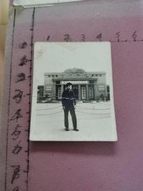 """老照片:一位男青年在武汉展览馆前留影(武汉展览馆挂""""湖北省工农业展览""""横幅、大门上有""""毛主席万岁""""标语)"""