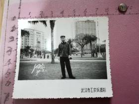 """老照片:一位男士在广州某大楼前留影(大楼大门正中挂毛主席像、像两侧挂""""伟大的中国共产党万岁""""""""伟大的领袖毛主席万岁""""条幅、楼顶有""""永远忠于毛主席""""、尺寸:8×6.8cm、含底片)"""