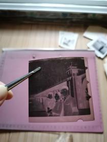 """老照片:一家三口在武汉长江大桥合影底片(其中男士臂戴袖章、女士抱幼儿、桥头堡外墙有标语:全世界无产…、桥上有""""…干劲,力争上游…""""横幅、尺寸:5.7×5.7cm)"""