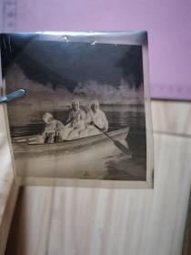 老照片:祖孙三口在某公园湖内划船合影底片(女童一手抱洋娃娃、一手持收音机在侧耳听)