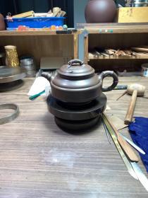 朱彩凤,可合影,国家级工艺美术师,双线竹鼓壶,壶体被线形相同而方向相反的双弧线分割后,形成上、中、下三部分,线形翻转排列极有节奏,对称中寓变化,配以竹节形流、把和钮。整器匀称,俏丽大方。紫砂壶