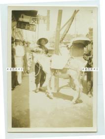 民国山东的街道街景老照片,店铺广告上写:邮便切手,代售邮票,火油,汽油,机油,电石,高级万年笔。