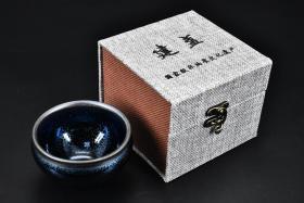 """(丙2313)《建盏》精装原盒一只  黑瓷代表 是中国宋代八大名瓷之一。 底部""""焦氏建盏""""款。建盏  因产地为宋建宁府瓯宁县,又因瓯宁县为建安附属县,故此称为建盏。 直径:9.3CM 高:6.2CM"""