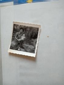老照片【妈妈抱着孩子坐在河边石头上】