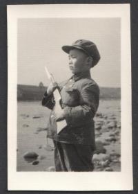 穿着一身小军装,手握木头玩具枪的小男孩