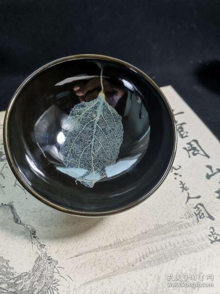 吉州窑天然木叶盏◆宋代独创,近代传承 ◆ 木叶蓝冰手工精品。尺寸/规格:口9.2高4.5厘米  吉州窑木叶盏,由天然桑叶高温烧制而成。精品叶脉清晰。叶子飘逸灵动。本堂新年专场拍卖吉州窑主人杯。都为现代仿古茶具。本堂为生产厂家线上直接上拍,一件也是批发,让每一位吉州窑木叶盏爱好者用最低的价格享受最高的产品体验。