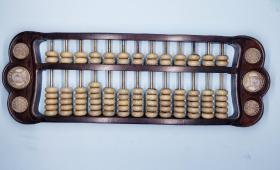 紫檀白玉籽算盘(檀木框架、92颗白玉算珠、两端镶嵌六枚银元)长42公分、宽14公分、重1.5公斤