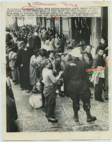 1948年新闻传真照片,上海粮食短缺,从香港运抵一批救济,白头盔的上海警察维持购买者的秩序
