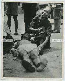 1939年7月19日湖北武汉,在日军暴风雨般轰炸中死去的平民,他的母亲在尸体边哭泣老照片