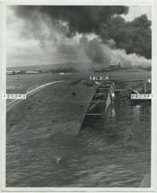 1941年12月7日日本偷袭美国太平洋海军舰队珍珠港老照片,基地一片惨状,近景的舰只已经倾覆沉没,远处的巡洋舰燃起滚滚黑烟。。