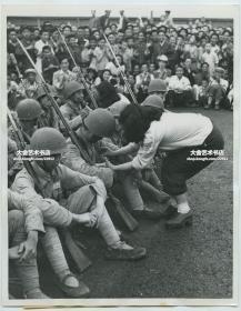 民国1949年8月19日上海解放后解放军进城,女学生为解放军士兵缝扣子,以表达对共产党子弟兵的欢迎老照片