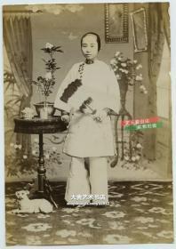 清代晚期民国早期拿鹅毛扇的年轻女子照相馆肖像老照片,小脚三寸金莲,一只小狗横卧桌子下