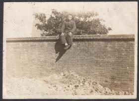 民国老照片,坐在墙头上的男人