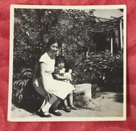 50-60年代 长辫子少妇与抱布娃娃的小女孩 脚穿一字皮鞋在花园里合影留念老照片