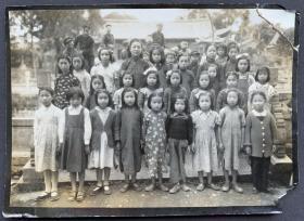 民国时期 小学校各年级女学生与一位女老师集体合影 银盐老照片一枚(穿着打扮各式各样,有旗袍、长袍、连衣裙、毛衣、花袄等,宛如多彩多姿的花朵,背后有调皮搞怪和看热闹的小男同学,背景学校应在庙宇内)