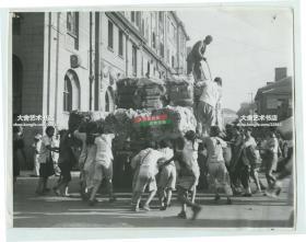 1946年上海黄浦区宁波路街道老照片,年轻人和孩子们哄抢一辆运输棉花的卡车,当时一斤棉花可以卖不少钱。当时国内内战的大背景下,秩序混乱。